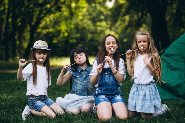 Grupo de turistas de meninas pela tenda na floresta
