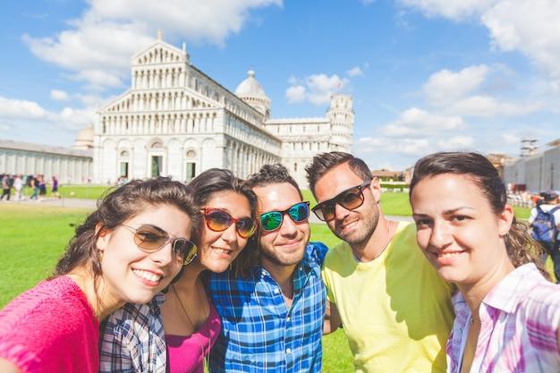 Grupo de turistas tomando uma selfie em pisa.