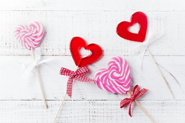 Grupo de vários doces festivos em forma de coração no fundo branco de madeira