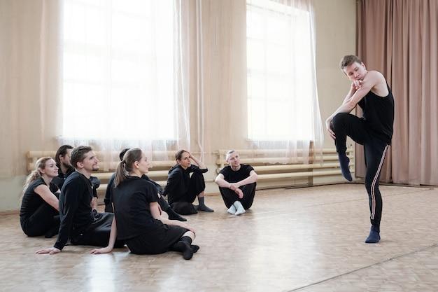 Grupo de vários jovens alunos do curso de dança sentados no chão enquanto olham para um cara vestindo roupas esportivas fazendo exercícios