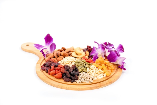 Grupo de vários tipos de frutas secas e grãos secos com linda orquídea em uma placa de madeira isolada no fundo branco.
