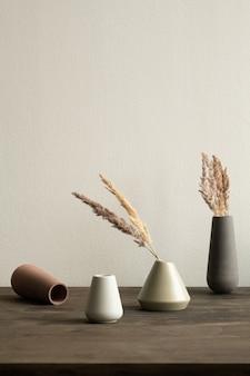 Grupo de vasos de cerâmica de cores brancas e marrons com plantas secas dentro de pé na mesa de madeira na parede dentro do quarto doméstico
