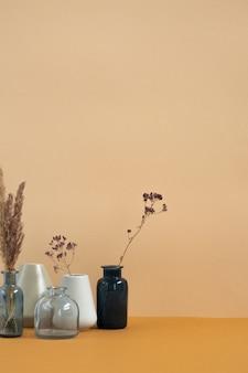 Grupo de vasos de cerâmica e vidro com flores silvestres secas e espinhos em cima da mesa na parede da sala doméstica ou estúdio de design
