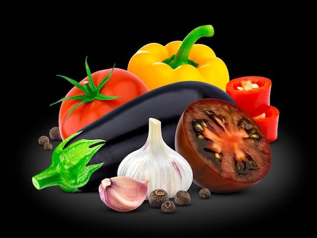 Grupo de vegetais, berinjela, tomate, pimenta e alho no preto.