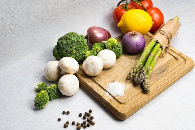 Grupo de vegetais frescos orgânicos espargos verdes e cogumelos brócolis em fundo cinza