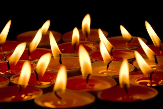 Grupo de velas em chamas no fundo escuro