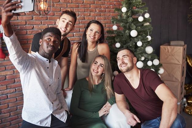 Grupo de velhos amigos se comunica e faz uma foto de selfie. ano novo está chegando. celebre o ano novo em um ambiente acolhedor