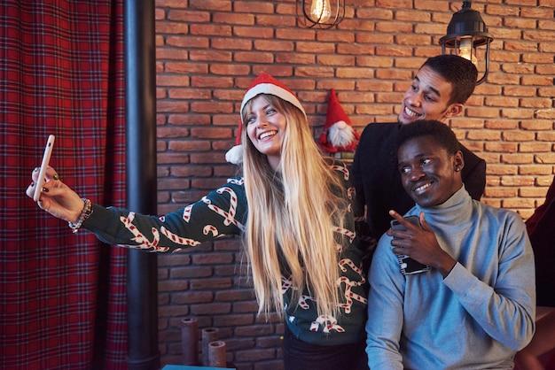 Grupo de velhos amigos se comunica e faz uma selfie. ano novo está chegando. celebre o ano novo em um ambiente acolhedor