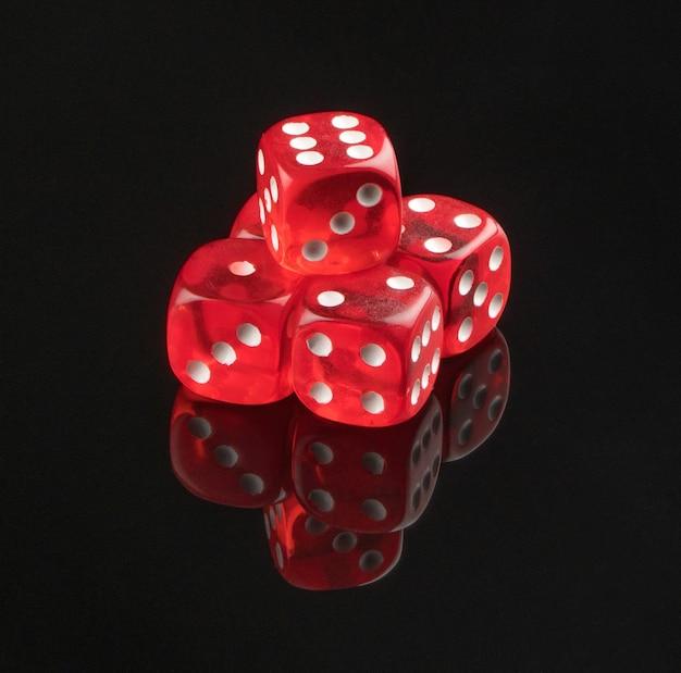 Grupo de vermelho jogando dados sobre um fundo preto com reflexão, isolado.