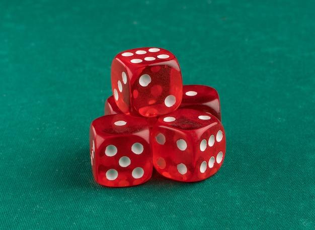 Grupo de vermelhos jogando dados sobre um fundo verde, isolado
