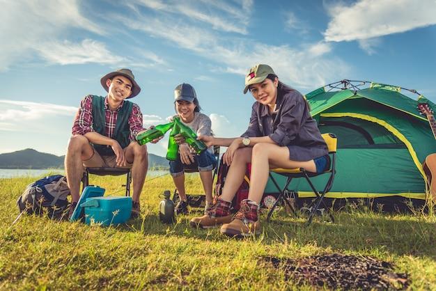 Grupo, de, viajantes, acampamento, e, piquenique, em, prado, com, primeiro plano barraca