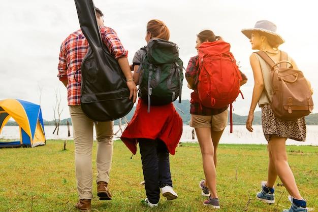 Grupo de viajantes familiares caminhando para o acampamento ao ar livre perto do lago para caminhadas no final de semana verão - conceito de viagens e recreação de férias