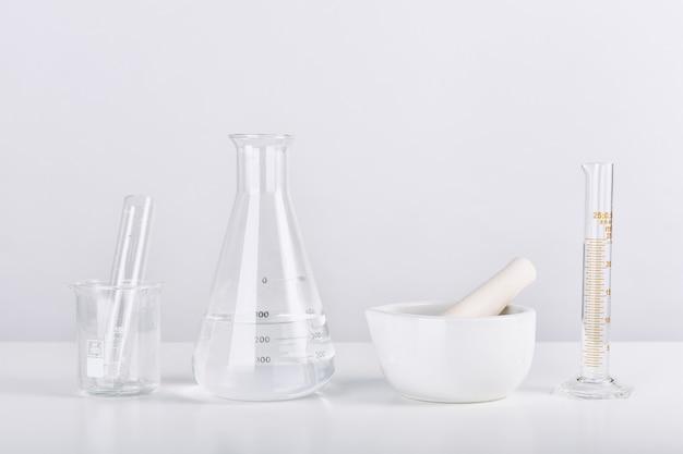 Grupo de vidro de laboratório científico e argamassa com solução líquida transparente, conceito de pesquisa e desenvolvimento.