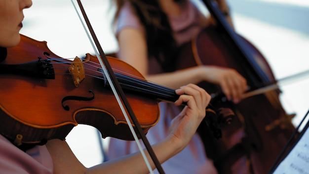 Grupo de violinistas e violoncelista no terraço