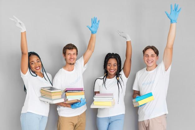 Grupo de voluntariado segurando livros para doações