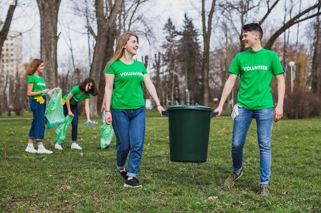 Grupo de voluntários carregando bin