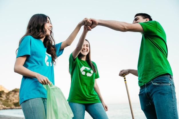 Grupo de voluntários coletando lixo na praia como uma equipe