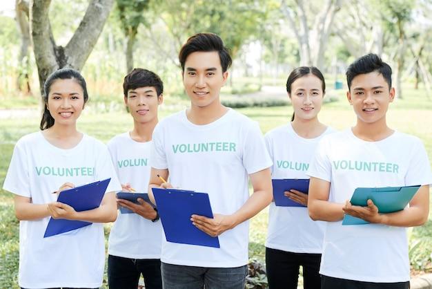 Grupo de voluntários com seu líder em pé no parque com uma prancheta nas mãos e olhando para a câmera