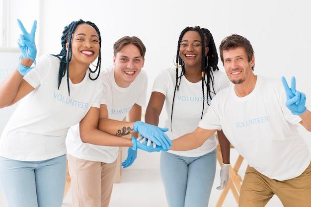 Grupo de voluntários de mãos dadas na frente