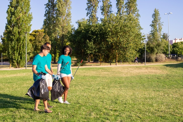 Grupo de voluntários ecológicos saindo do parque após a limpeza dos gramados