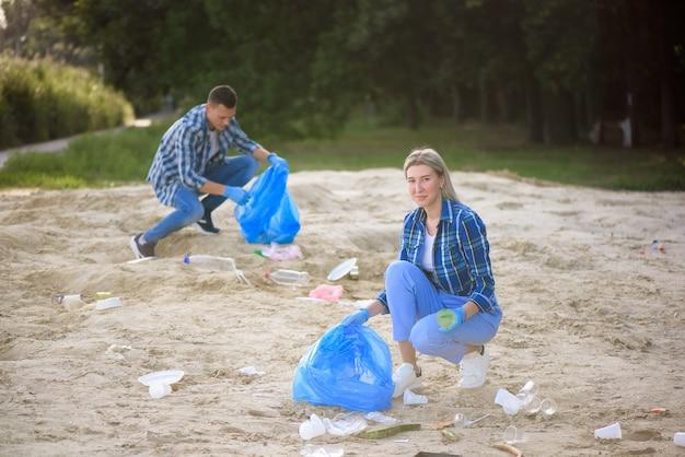 Grupo de voluntários felizes com sacos de lixo limpando a área do parque