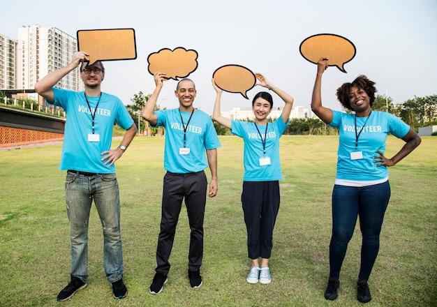 Grupo de voluntários felizes e diversos com bolhas do discurso