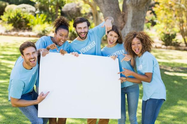 Grupo de voluntários, segurando uma folha em branco e apontando para ele
