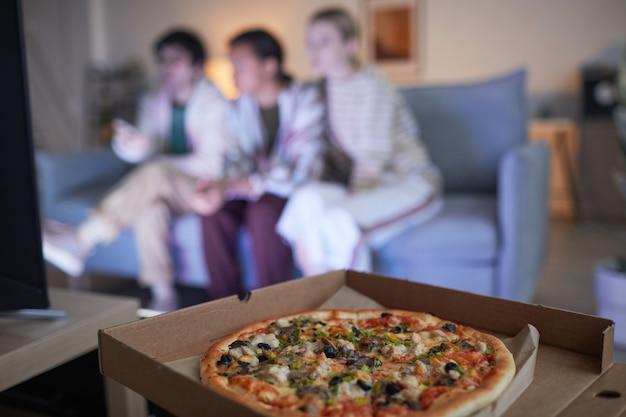 Grupo desfocado de amigos assistindo tv em casa iluminada por uma luz azul, foco na pizza em primeiro plano, espaço de cópia