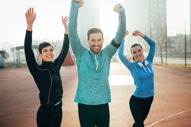 Grupo determinado de amigos felizes depois de atingir os objetivos de treinamento e esportes