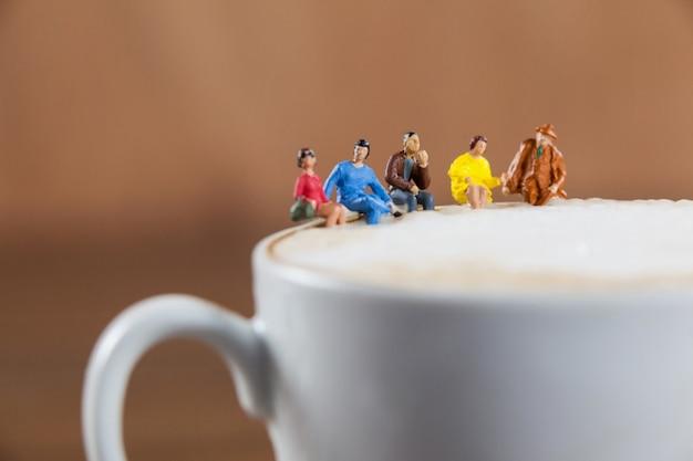 Grupo diminuto de amigos tomando café