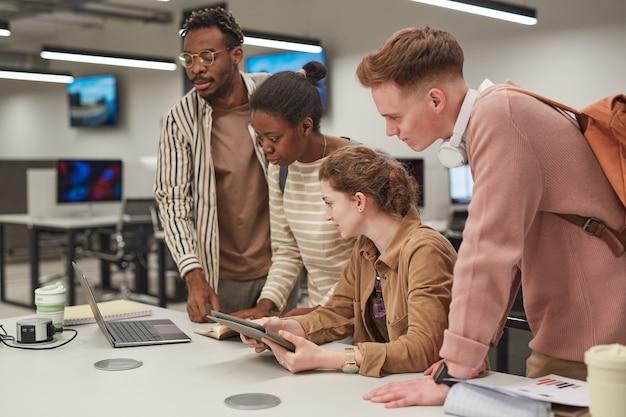 Grupo diversificado de alunos trabalhando juntos e usando computadores em pé à mesa no laboratório de ti da escola