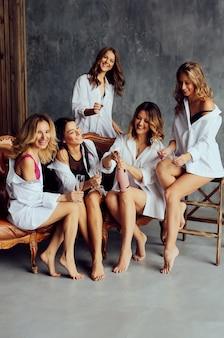 Grupo diversificado de amigas desfrutando de uma festa e rindo. amigos de mulheres dando uma festa.