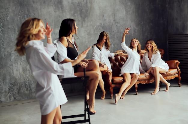 Grupo diversificado de amigas desfrutando de uma festa e rindo. grupo de mulheres bonitas que têm o divertimento e que sentam-se no sofá.