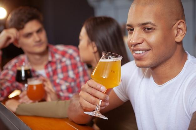 Grupo diversificado de amigos bebendo cerveja no bar juntos