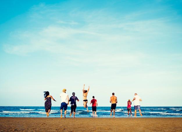 Grupo diversificado de amigos correndo para a praia