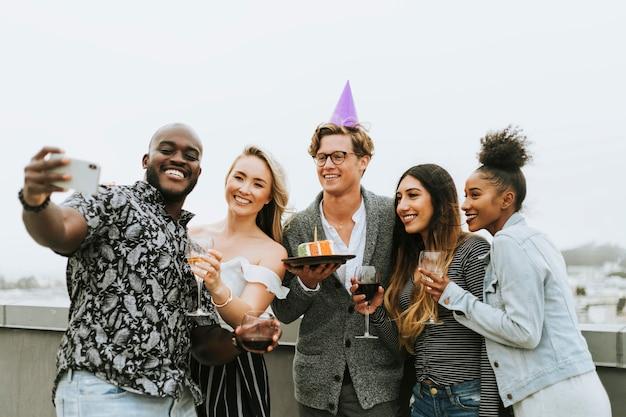 Grupo diversificado de amigos tomando uma selfie em uma festa de aniversário
