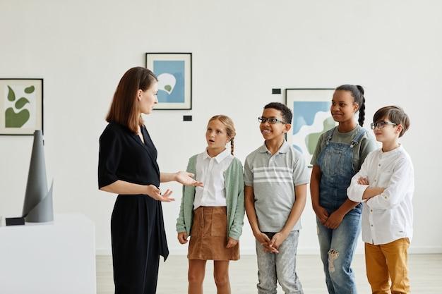 Grupo diversificado de crianças ouvindo uma especialista feminina em uma galeria de arte moderna, copie o espaço