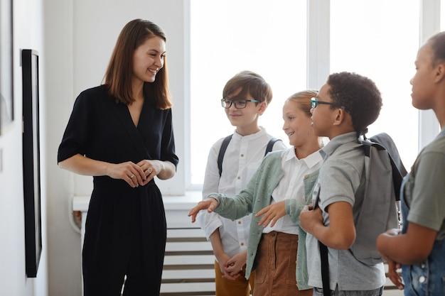 Grupo diversificado de crianças ouvindo uma guia turística enquanto visitava a galeria de arte moderna, copie o espaço
