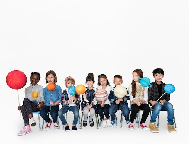 Grupo diversificado de crianças segurando planetas em varas isolado fundo