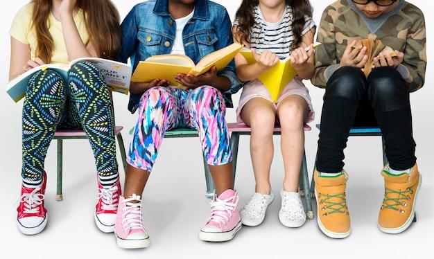 Grupo diversificado de crianças sentadas em uma fila lendo livros