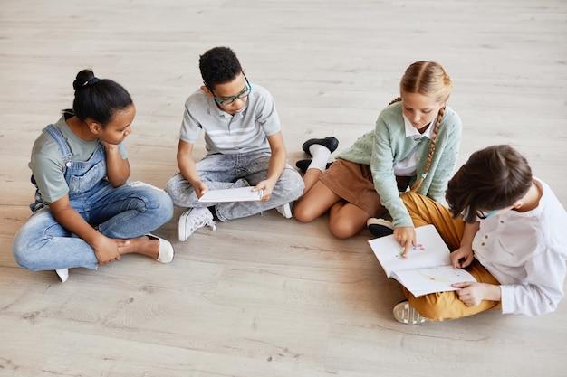 Grupo diversificado de crianças sentadas no chão da escola discutindo fotos