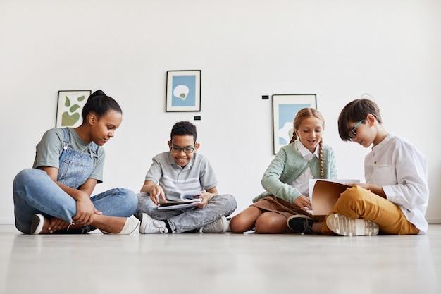 Grupo diversificado de crianças sentadas no chão em uma galeria de arte discutindo pinturas