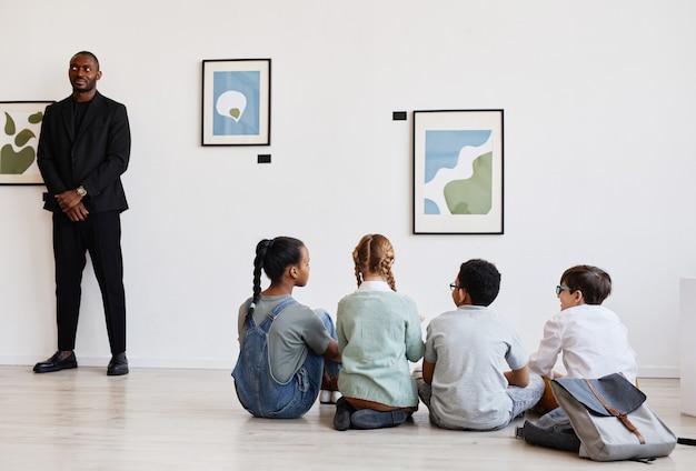 Grupo diversificado de crianças sentadas no chão em uma galeria de arte moderna discutindo pinturas, copie o espaço