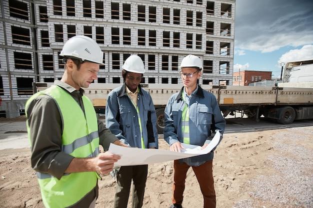 Grupo diversificado de engenheiros discutindo plantas baixas no espaço da cópia do canteiro de obras