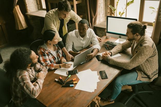 Grupo diversificado de freelancers brainstorming em coworking
