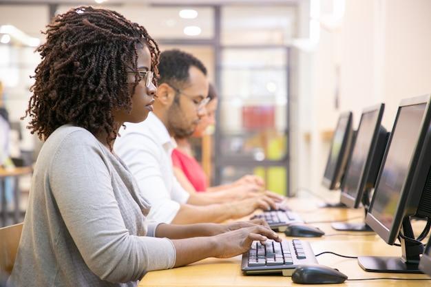Grupo diversificado de funcionários trabalhando em seus computadores