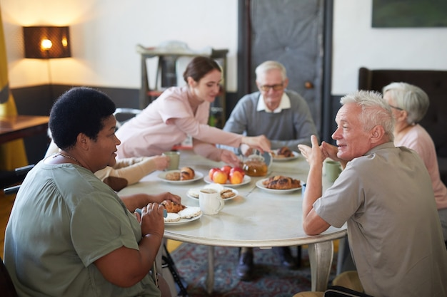 Grupo diversificado de idosos tomando café da manhã em uma mesa redonda em um moderno asilo.