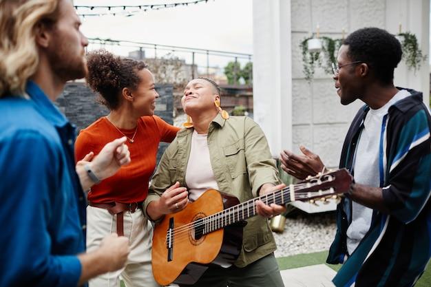 Grupo diversificado de jovens tocando violão e se divertindo enquanto desfrutam de uma festa ao ar livre na cobertura