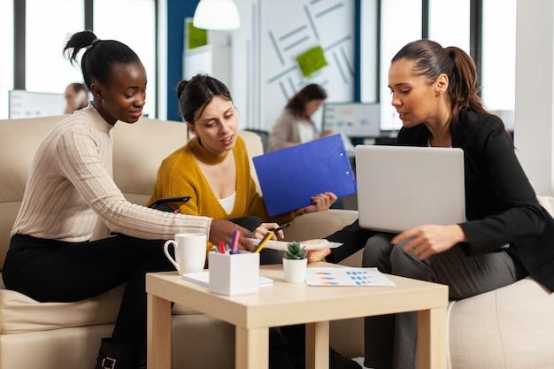 Grupo diversificado de mulheres de negócios, sentadas no sofá no escritório de uma empresa moderna de inicialização corporativa, falando sobre o projeto financeiro inicial e gerenciamento de estratégia, usando laptop e gráficos