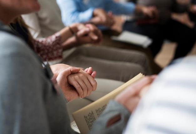 Grupo diversificado de pessoas de mãos dadas no grupo de apoio